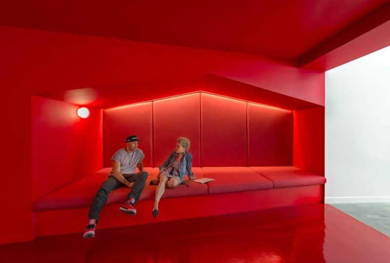 stunningly-bright-red-corridors-link-the-working-areas-together-this-hallway-even-has-a-couch-built-in